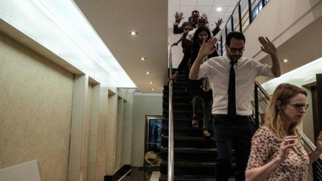 Varias personas bajan una escalera con los brazos arriba