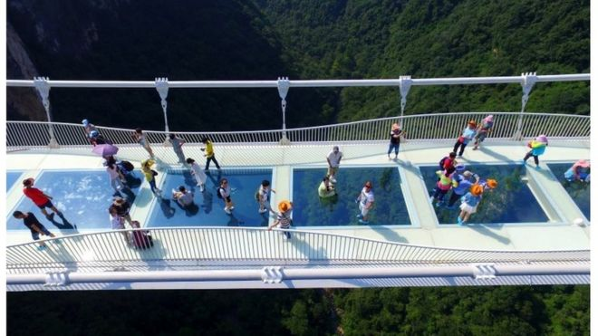 visitors walk across a glass floor suspension bridge in zhangjiajie in southern chinas hunan province - Zhangjiajie Glass Bridge