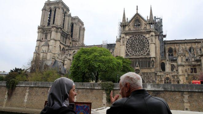 Una monja y un cura observan la catedral de Notre Dame el día después del incendio.