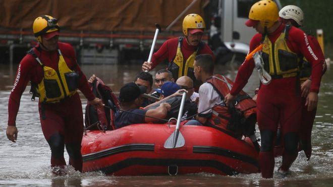 Bombeiros usam bote para resgatar pessoas ilhadas em enchente