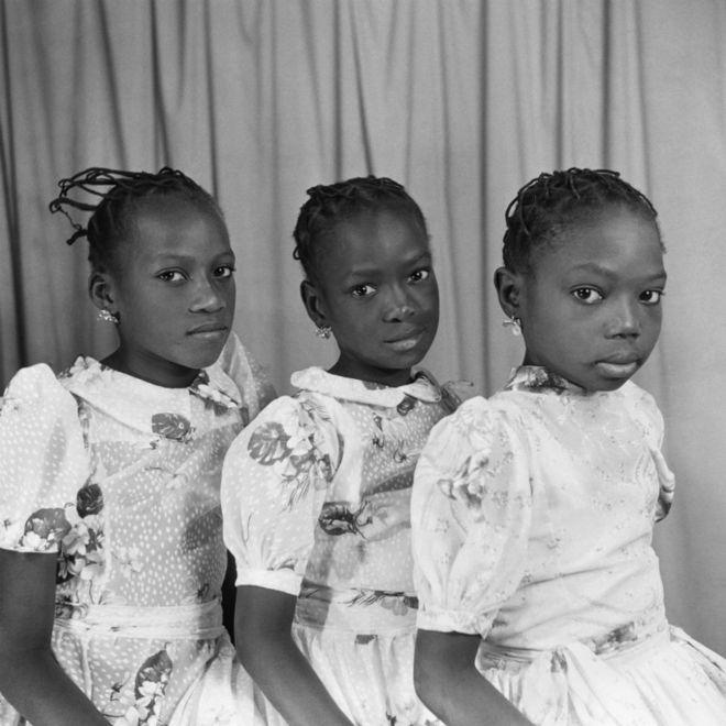 Des jeunes filles portant des robes, des boucles d'oreilles et des coiffures assorties posent devant la caméra.