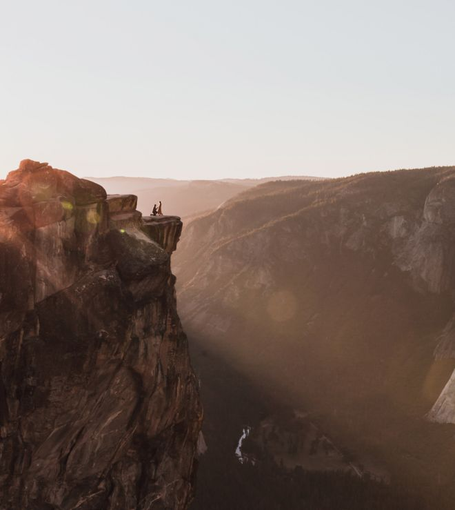 A dramatic shot shows a couple on a ledge at Taft Point in Yosemite