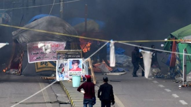 Iraqi security forces (in the background) burn protesters' tents at Tahrir Square in central Baghdad. photo: 25 January 2020