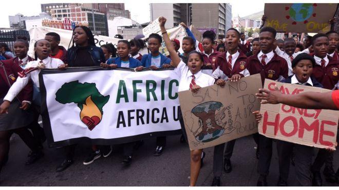 Jóvenes con pancartas Sudáfrica cambio climático