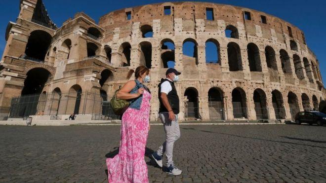 Dos personas con mascarilla frente al Coliseo de Roma.
