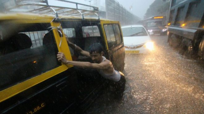 A man pushes a taxi through a waterlogged street during heavy rains in Mumbai, India on 01 July 2019