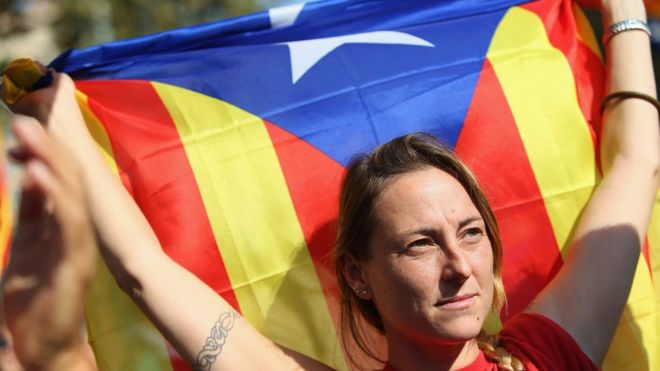 A Catalan independence supporter holds a Catalan flag