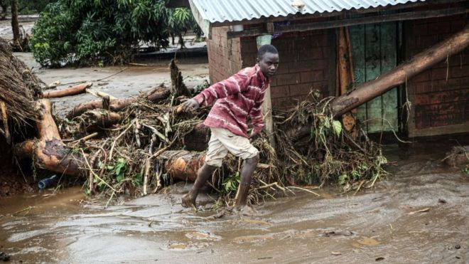 A 12-year-old boy walks through the mud after River Muruny burst its bank following heavy rains in Parua village, about 85 km northeast of Kitale, in West Pokot county, western Kenya on November 24, 2019.