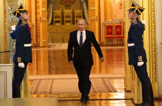 O presidente russo Vladimir Putin entra em salão no Kremlim, no meio de dois guardas