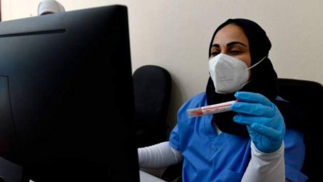 امرأة تجلس أمام حاسوب