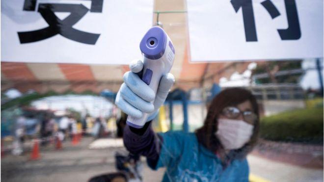 Um funcionário usando uma máscara facial mede a temperatura de um visitante em um parque temático no Japão.