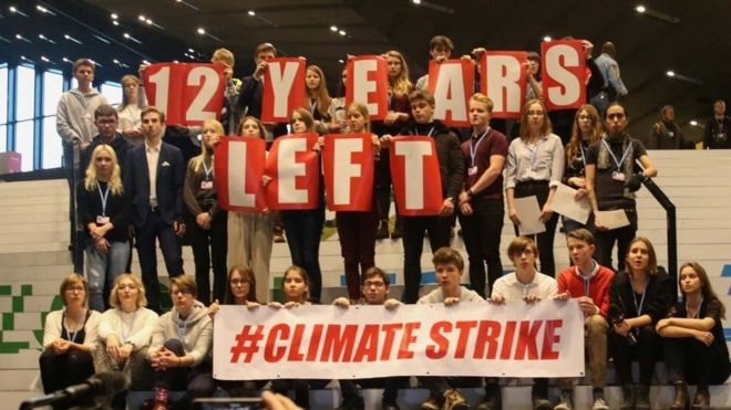 Demonstrators hold a slogan at UN climate talks in Katowice, Poland