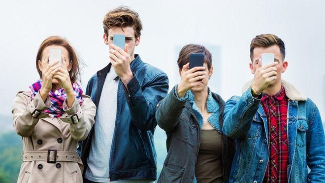 Cuatro jóvenes con los rostros tapados por sus teléfonos celulares, una imagen que busca crear la idea de la adicción a las redes