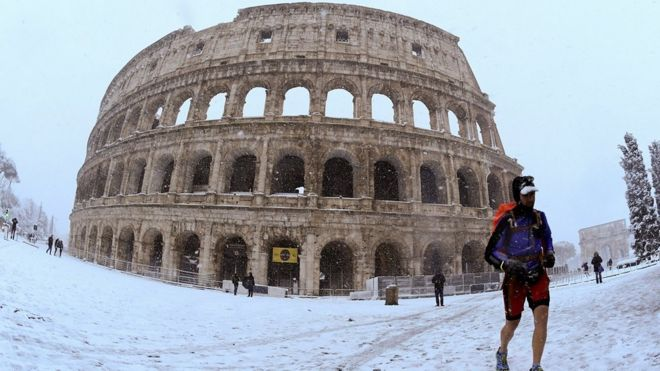 A man runs during heavy snowfall in front of the Colosseum in Rome