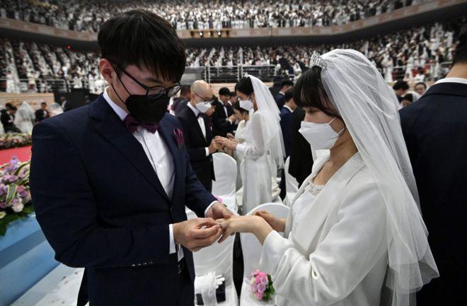 الأزواج يتبادلون خواتم الزواج في حفل زفاف جماعي نظمته كنيسة التوحيد في غابيونغ