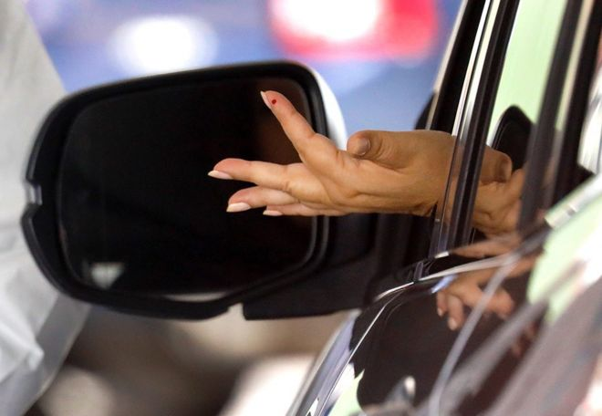امرأة تمدّ يدها خارج شباك السيارة