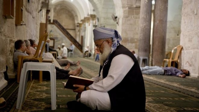 An elderly man reads the Quran in a West Bank mosque