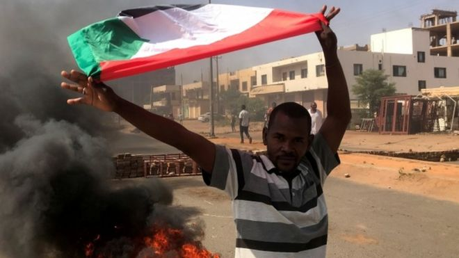 A protester in Sudan waves a flag