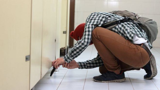 A Man Takes A Photo Under A Toilet Door Stock Photo