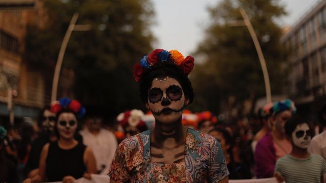 A woman with full skull make-up and flower headband on