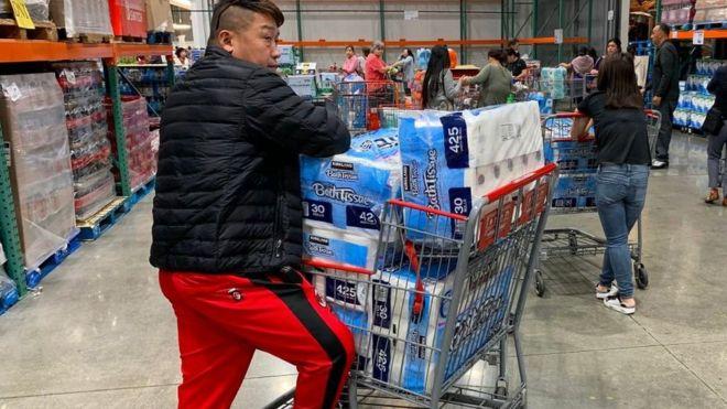 Un hombre con cinco paquetes grandes de papel higiénico en California