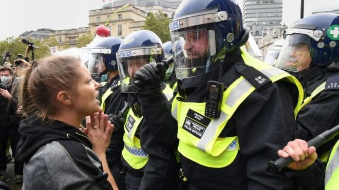 """Protesters and police at a """"We Do Not Consent"""" rally at Trafalgar Square in London"""