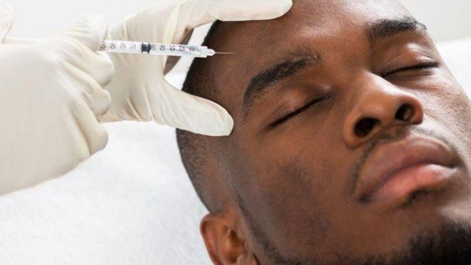 Un hombre se somete a una inyección en la frente