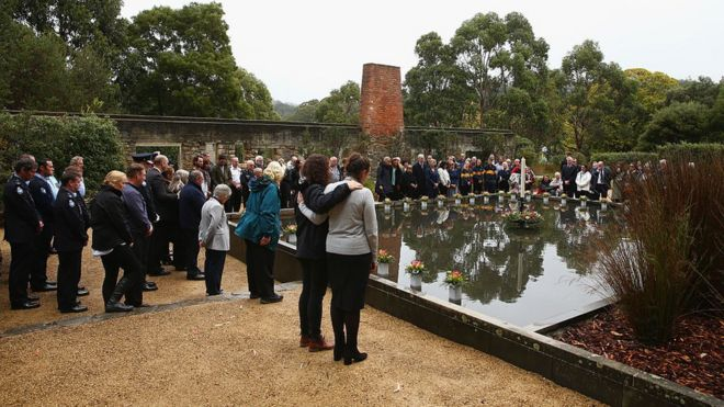 People stand at the Port Arthur memorial site during a commemoration service in 2016 to mark the 20th anniversary of the massacre