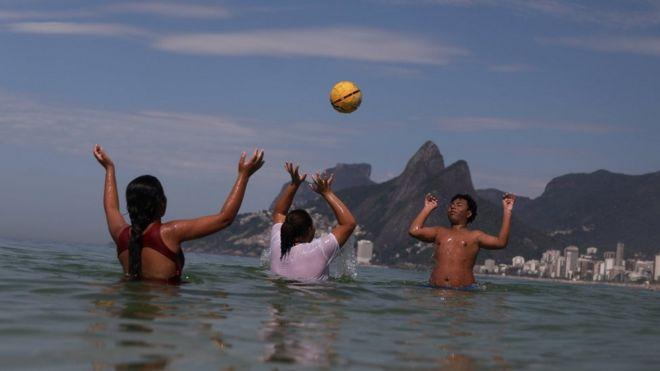 adolescentes jogam bola dentro do mar no Rio de Janeiro