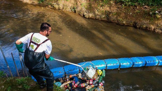 Diego retirando lixo do rio que ficou retido na barreira que criou