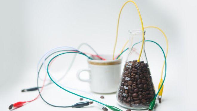 Xícara de café cheia de fios e balão de Erlenmeyer com grãos de café