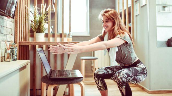 Una mujer haciendo sentadillas frente a una laptop.