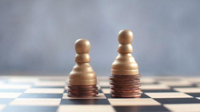 Tabuleiro de xadrez com duas peças apoiadas sobre moedas - uma em uma pilha mais baixa que a outra