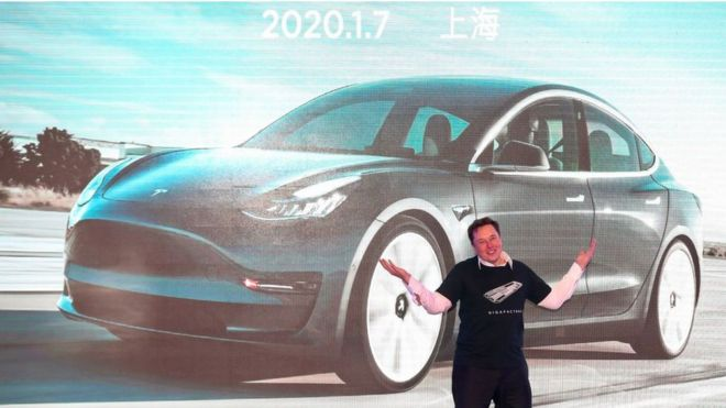 Elon Musk on stage in front of an image of a Tesla Model 3