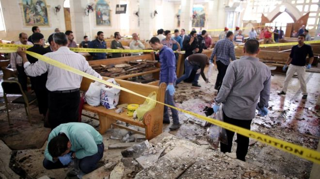 Security personnel investigate the scene of a bomb explosion inside Mar Girgis church in Tanta