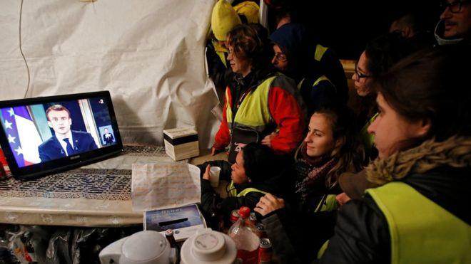 Những người biểu tình áo vàng theo dõi diễn văn của Tổng thống Emmanuel Macron qua tivi