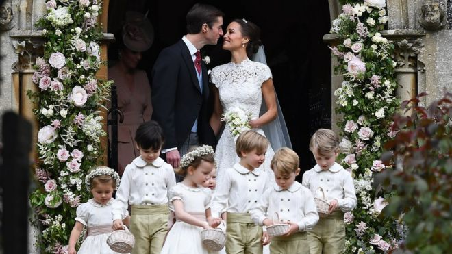 Pippa Middleton and James Matthews in the arch of the church they married in with seven page boys and bridesmaids in front of them.