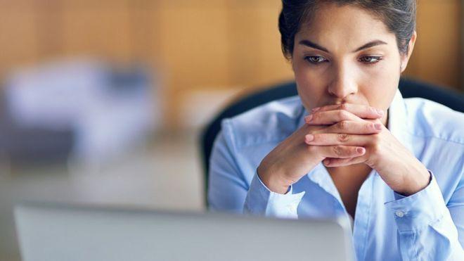 Mujer mirando una pantalla de computador