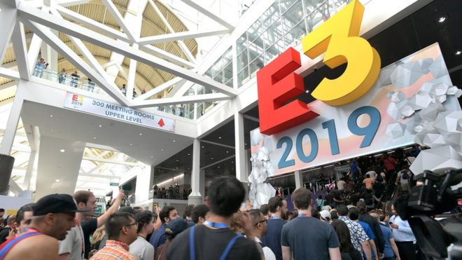 The E3 logo sits above a door as hundreds of attendees flow through the entrance into the conference centre
