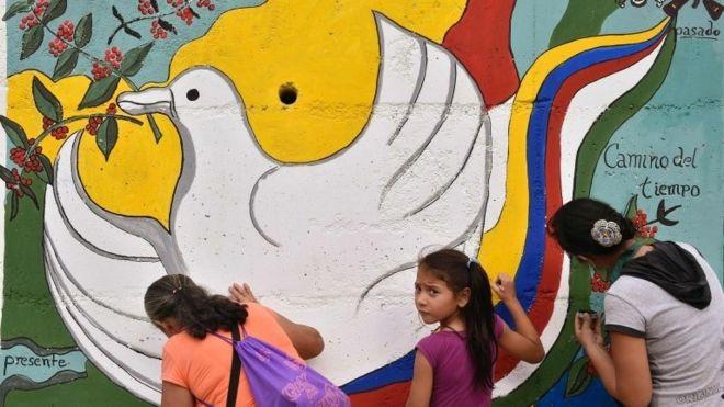 Женщины и девушка рисуют фреску, намекая на мир на дороге, ведущей в Планадас, департамент Толима, Колумбия (26 августа 2016 года)