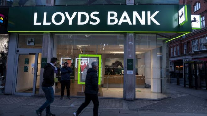 People walk past Lloyds bank branch