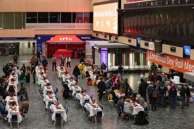 Network Rail volunteers and those from other charities welcome the homeless into the departures and arrivals hall at Euston Station for a Christmas meal, 25 December