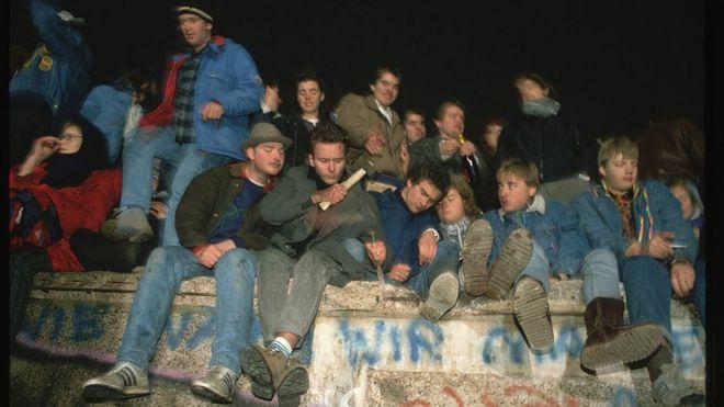 Una docena de personas celebran la apertura de la frontera encima del Muro de Berlín.