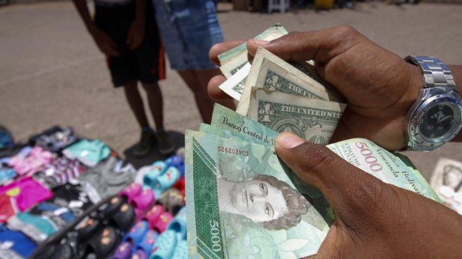 Hombre sostienen dólares y bolívares