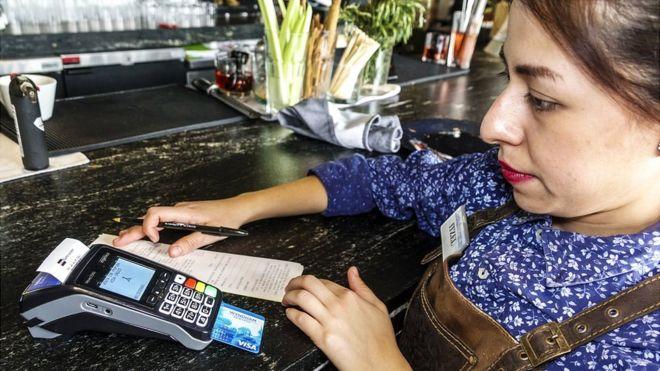 Mesera con tarjeta de crédito en América Latina.