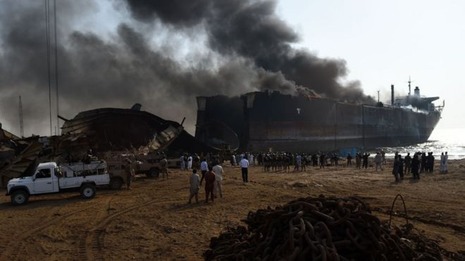 Pakistani bystanders gather around the wreckage of a burning ship after a gas cylinder explosion at the Gadani shipbreaking yard, some 50 kilometres (30 miles) west of Karachi on 1 November, 2016