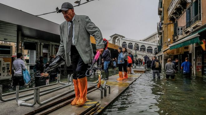 People walk across temporary walk ways in Venice on 29 October 2018