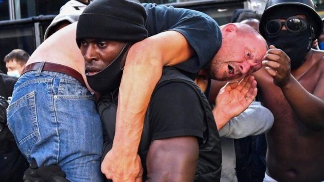 Patrick Hutchinson (centro) cargando un manifestante
