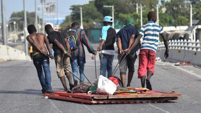 Looters carry away items in Delmas, a commune near Port-au-Prince, during protests against the rising price of fuel, on July 8, 2018.