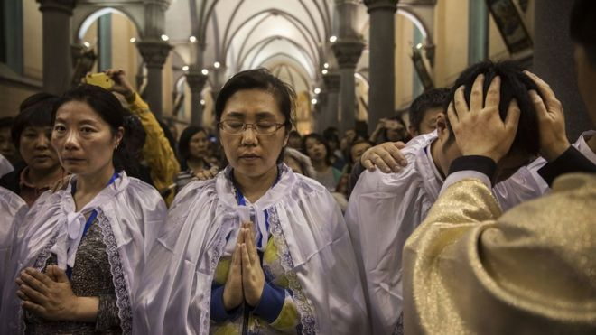 Chinese Catholic Bishop Zhang Hong, right, blesses newly baptized worshippers during a special ceremony at a mass on Holy Saturday during Easter celebrations at the government sanctioned West Beijing Catholic Church on April 15, 2017 in Beijing, China. China, an officially atheist country, places a number of restrictions on Christians, allowing legal practice of the faith only at state-approved churches.